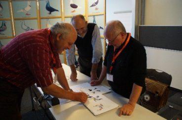 Heinrich Niederklopfer und Claude Schneider nutzten die Chance, um letzte Details an den Standardbildern der Schweizer Tauben mit dem Zeichner Jean-Louis Frindel abzusprechen. Foto: Bauer